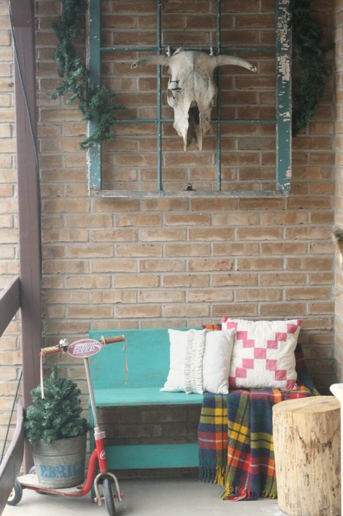 Christmas porch entry, vintage pillows and plaid blanket, turquoise bench and window, radio flyer scooter, bull skull