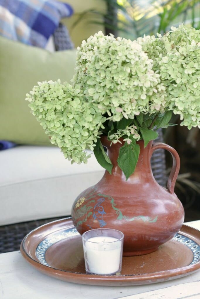 Mexican pitcher filled with hydrangeas on Fall porch