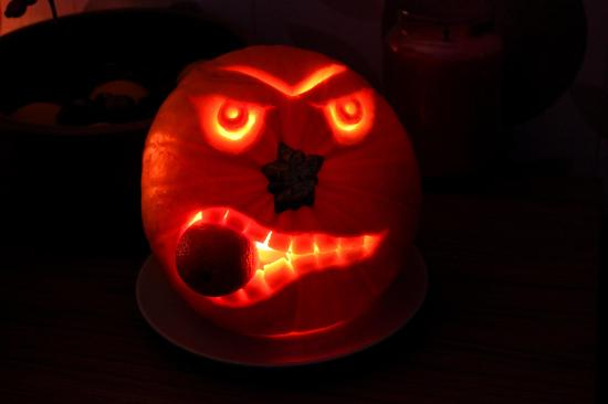 angry halloween pumpkin carved eating an orange