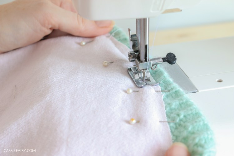 Photo of pink and green fabric being stitched together with a sewing machine