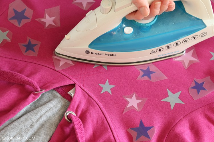 Photo of heat-transfer vinyl stars being applied to a hoody