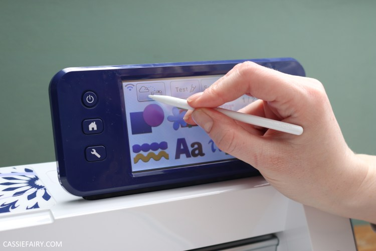 Photo of a stylus being used to select a t-shirt design on an electronic cutting machine.