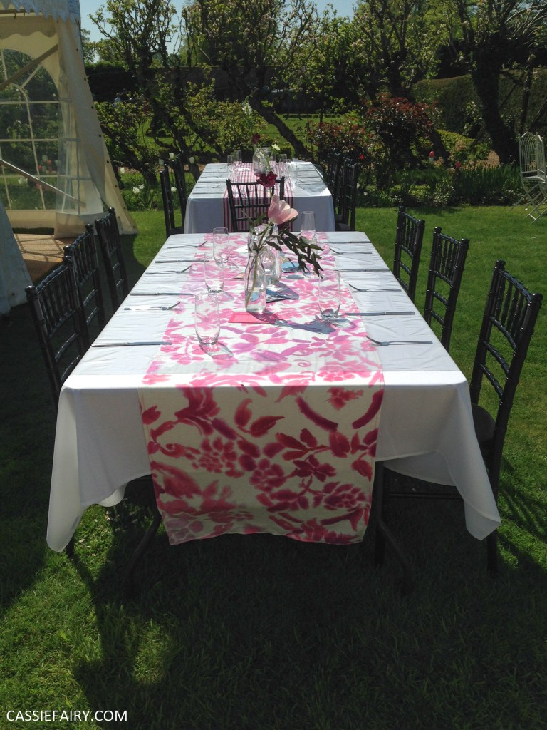 outdoor wedding reception with pink tablecloth and flowers in jam jars