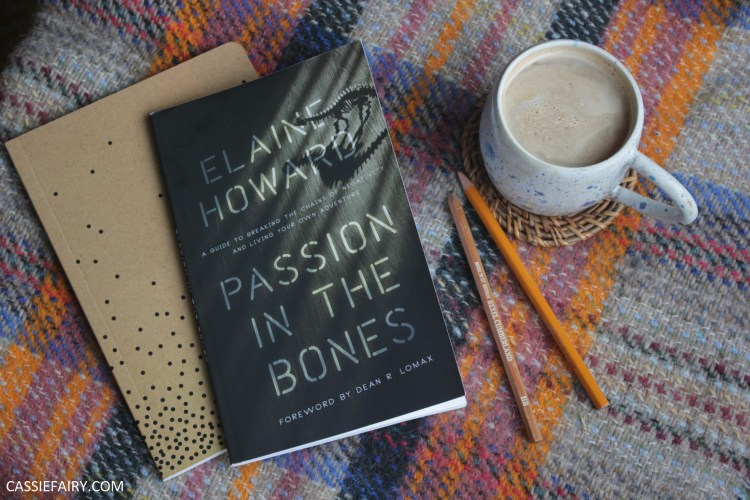 Passion in the Bones book on a rug, beside a notebook, pencils and mug of coffee