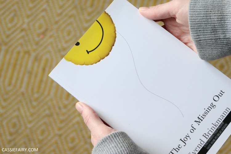 photo of two hands holding a copy of the joy of missing out book