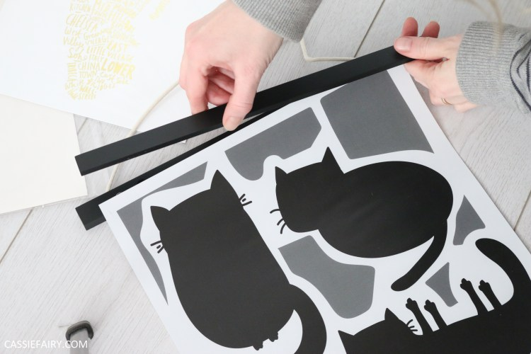 magnetic hanging frame being applied to a poster print of black and white cats