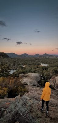 A woman in a yellow coat looks over the view at the Pagoda Lookout in Wollemi National Park