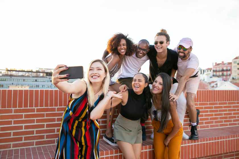 excited young diverse men and women taking selfie on rooftop