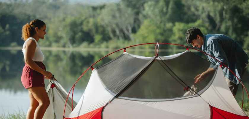 diverse hikers putting up tent against river