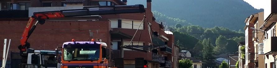 Tallen un tram de l'avinguda Catalunya de Castellbell i el Vilar per muntar una estructura metàl·lica a un camió.