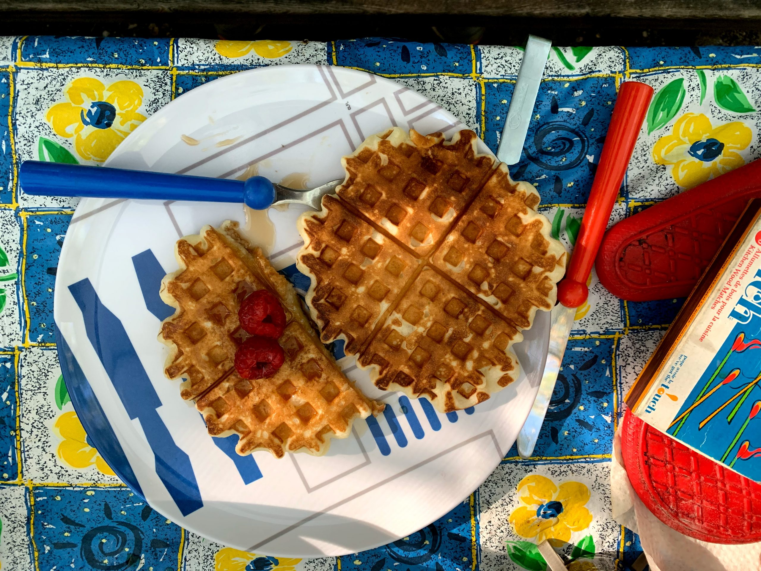 A plate of waffles on a colourful plate and picnic table setting.