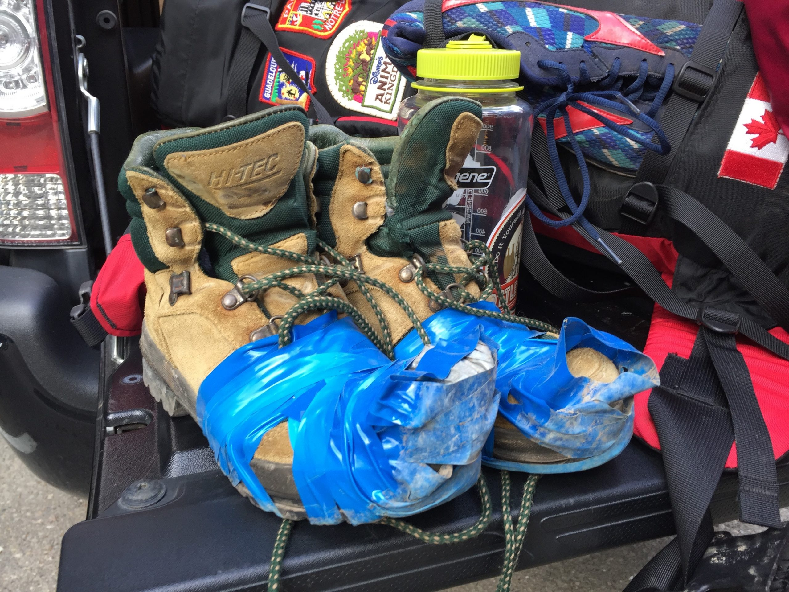 A pair of nearly-destroyed hiking boots wrapped in blue tape sit in a pile of hiking gear.