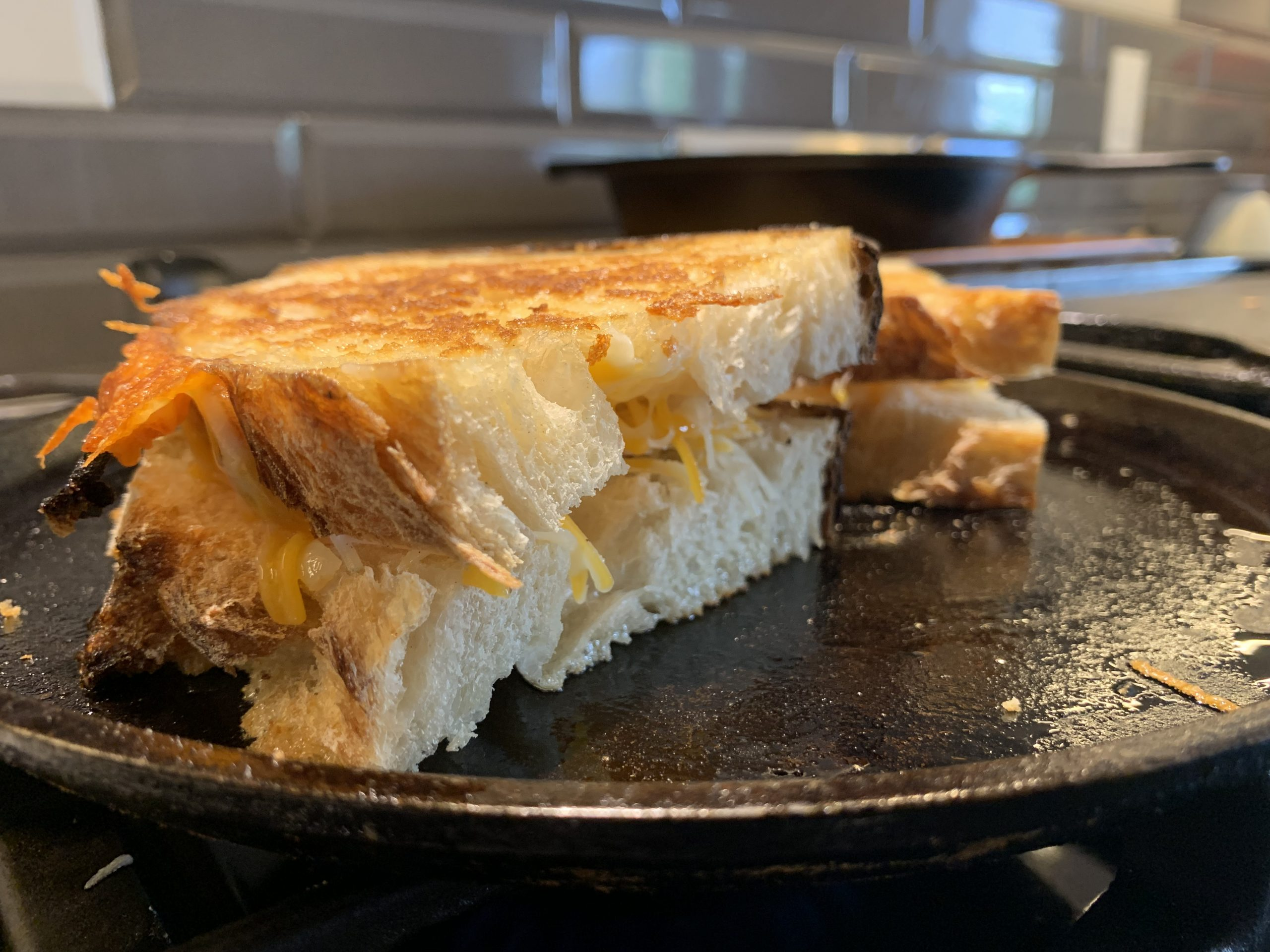 A simple grilled cheese sandwich on a flat cast iron pan.