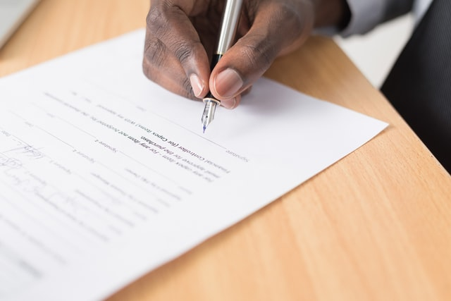 dark-skinned hand signing a document with a silver fountain pen