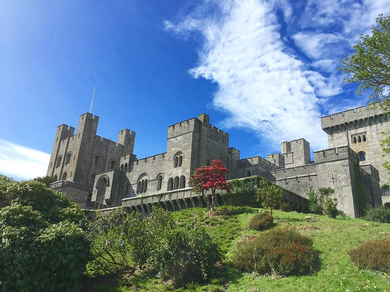 The exterior of Penrhyn Castle standing proudly on a hilltop