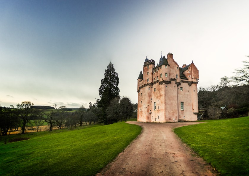Scotland's pink Craigievar Castle with a dirt path leading up to the structure