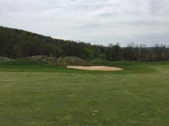 Fairway bunker on 5th hole with shrubbery around it.