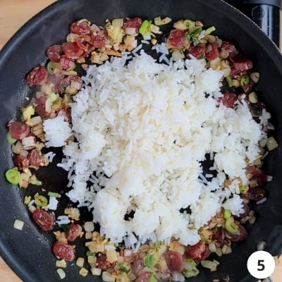 White rice poured into the centre of pan with sausages and onions pushed to the sides of pan
