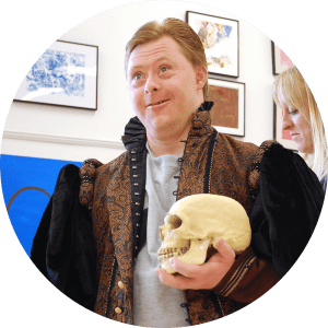 Photo of smiling CATA artist Dan wearing a Shakespearean costume and holding a skull