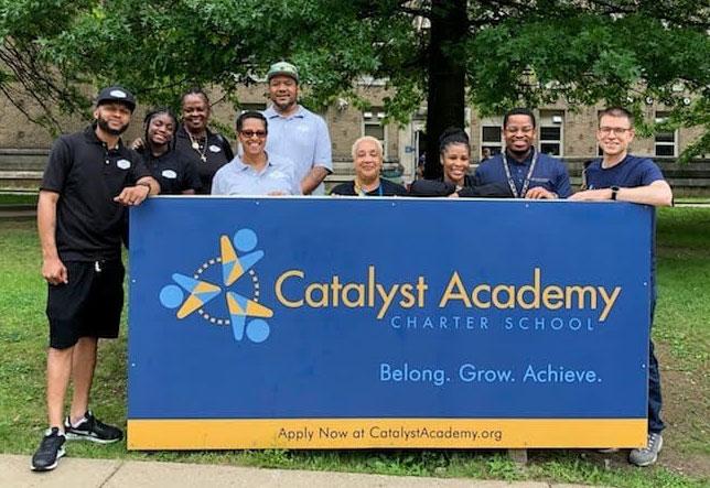 Catalyst Academy staff standing behind Catalyst Academy banner