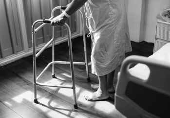 person holding medical walker beside white hospital bed