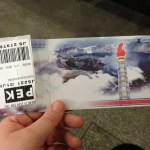 Back of the plane ticket - this lake inside a mountain is near where Kim Il-Sung was born and features in a lot of pictures. The flame is a symbol of the Kims being eternally with the Korean people, even though they are physically gone.