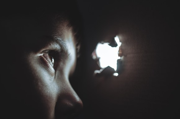 person looking at small hole of light