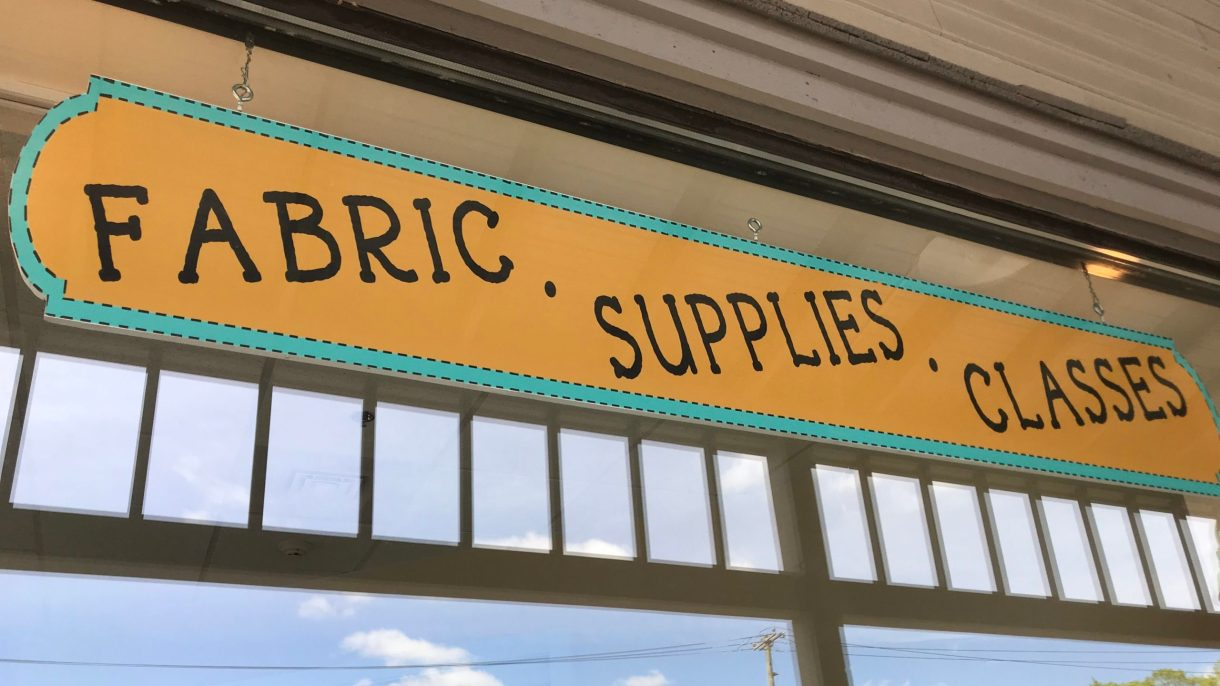 "A sign outside the store that says ""Fabric,"" ""Supplies,"" and ""Classes."""