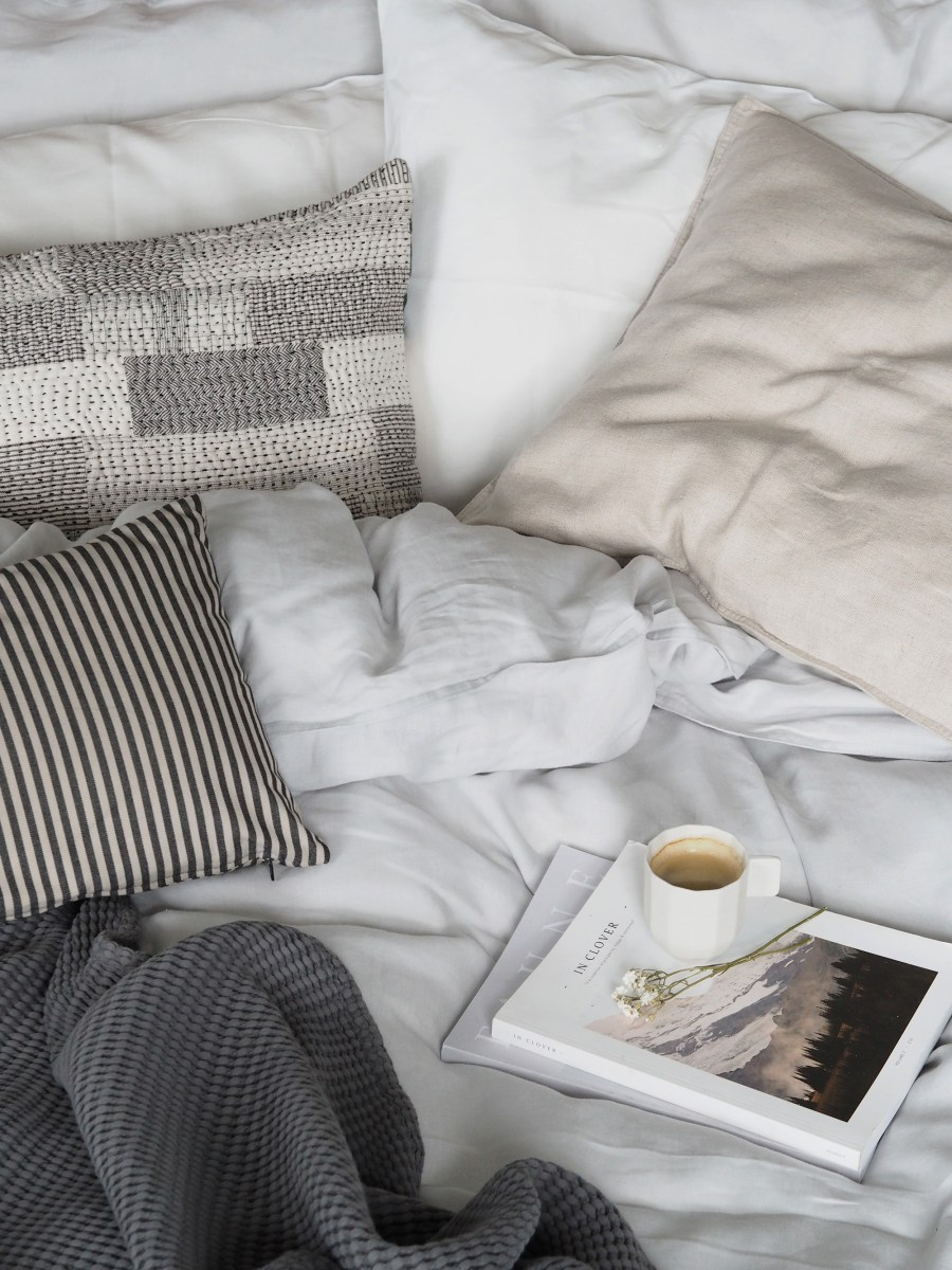 Light Scandi style bedroom with French linen bedding. White bed linen, striped cushion. How to care for your bed linen, with eco-friendly dry cleaners BLANC London [AD]