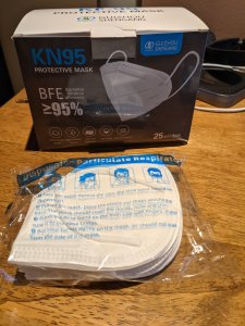 Photograph of a box of KN95 Masks purchased from Newegg. In front is a pack of masks from inside the box.