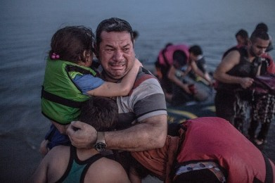 Laith Majid holding his son and daughter breaks out in tears of joy after arriving on the shore of the island of Kos in Greece.