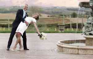 Groom dipping bride by a Glenwood fountain