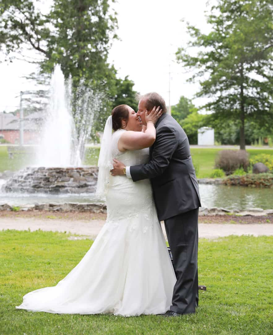 First kiss as bride and groom with park fountain behind them