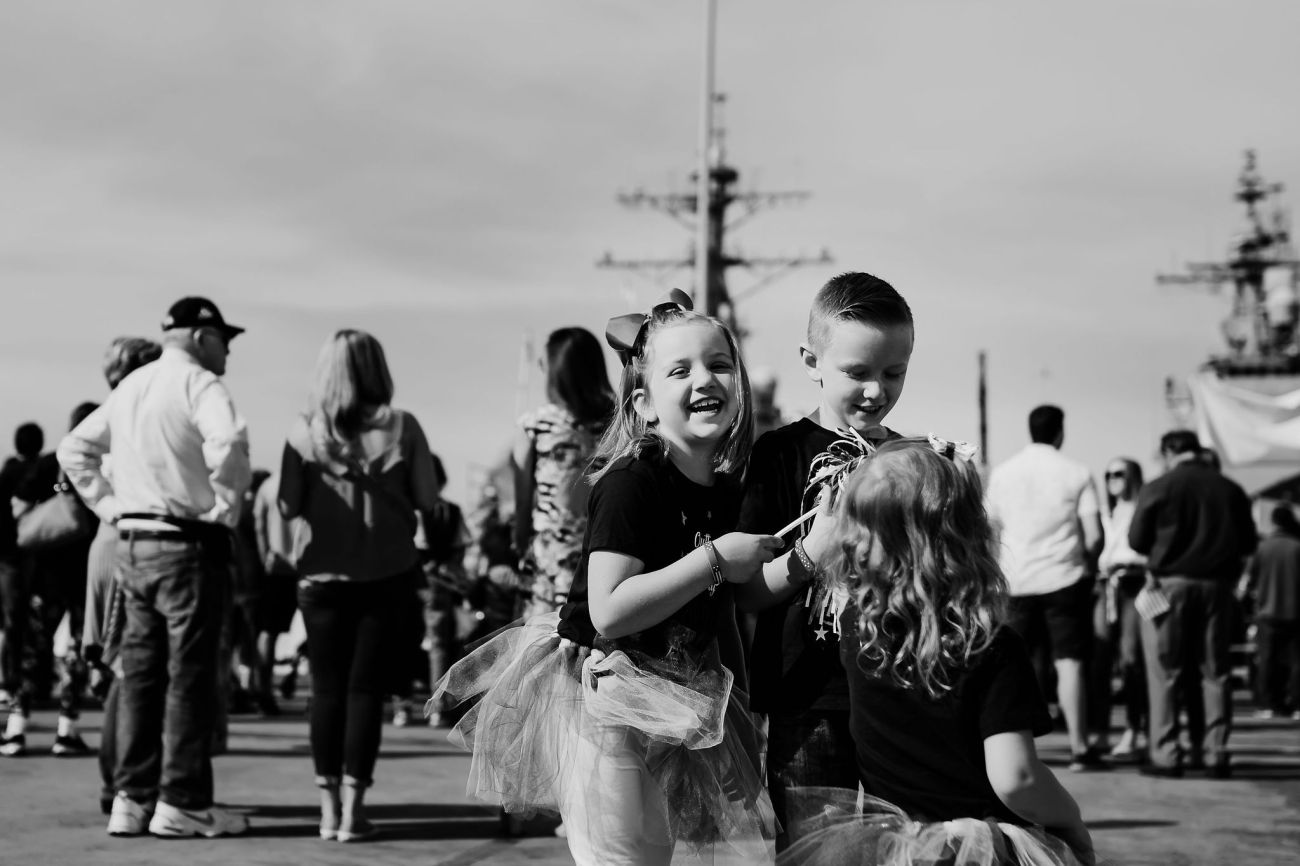 san diego navy husband military homecoming smiling hugging wife and children {virginia beach lifestyle newborn child couples family maternity engagement photographer}