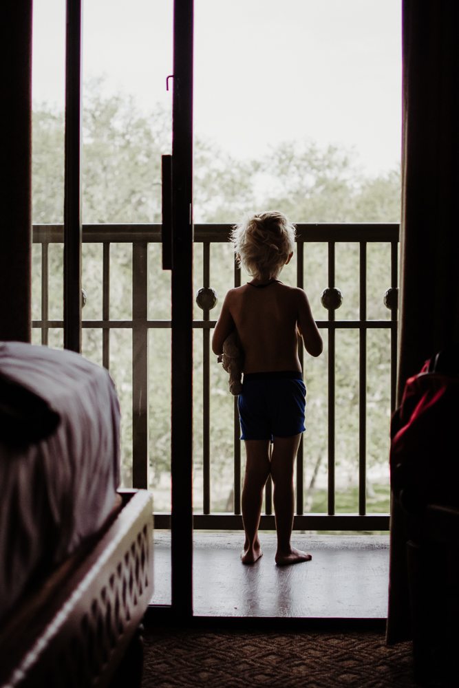 little boy in undies holding teddy bear looking out patio disney world animal kingdom lodge {virginia beach lifestyle newborn child couples family maternity engagement photographer}