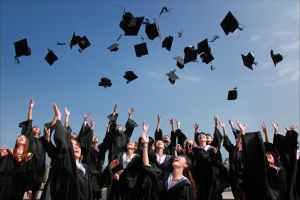 People throwing graduation hats into air