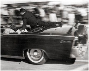 Service agent Clinton Hill shielding the occupants of President Kennedy's limousine.