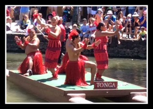 Dancing atop a double-hulled canoe in the canal at Polynesian Cultural Center.