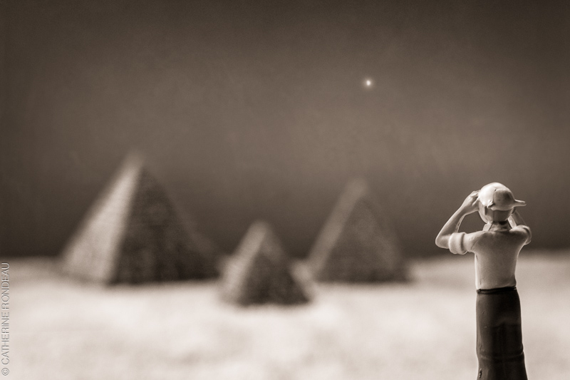 Figurine of a man looking towards miniature pyramids.
