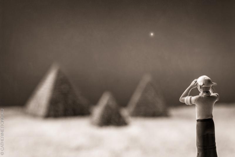 Figurine of a man looking towards miniature pyramids.