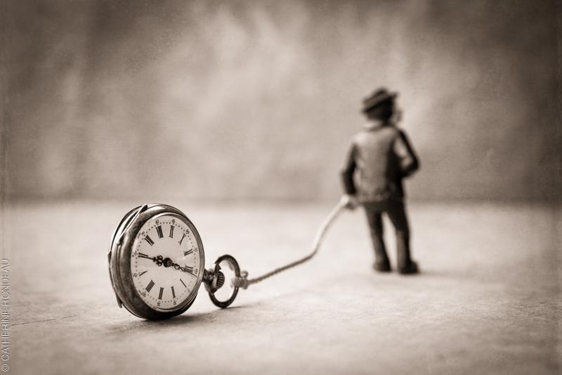 Figurine d'un homme qui traine une corde rattachée à une montre ancienne.