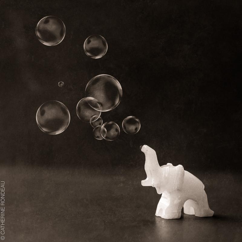 Figurine d'éléphant blanc qui semble faire des bulles de savon.