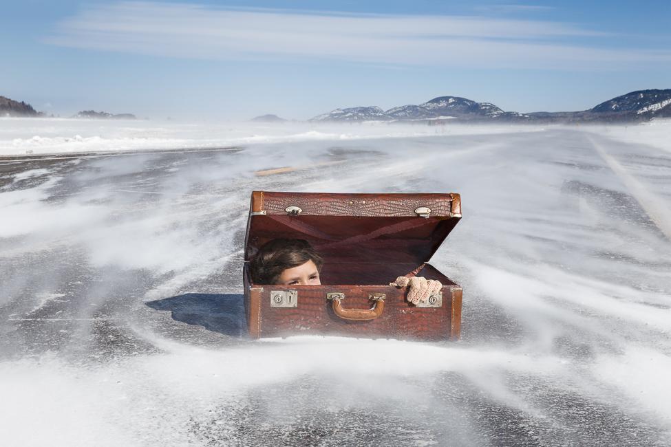 Le visage d'une adolescente émerge d'une valise posée sur une route enneigée.