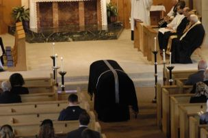 As the sequence is sung, the casket is seen before the altar, surrounded by six large candles.