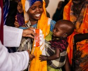 Adeego Adan Hussein is assisted by hospital staff in feeding her daughter, Deeqa Ibrahim, with Plumpy Sup. Photo: Amunga Eshuchi.