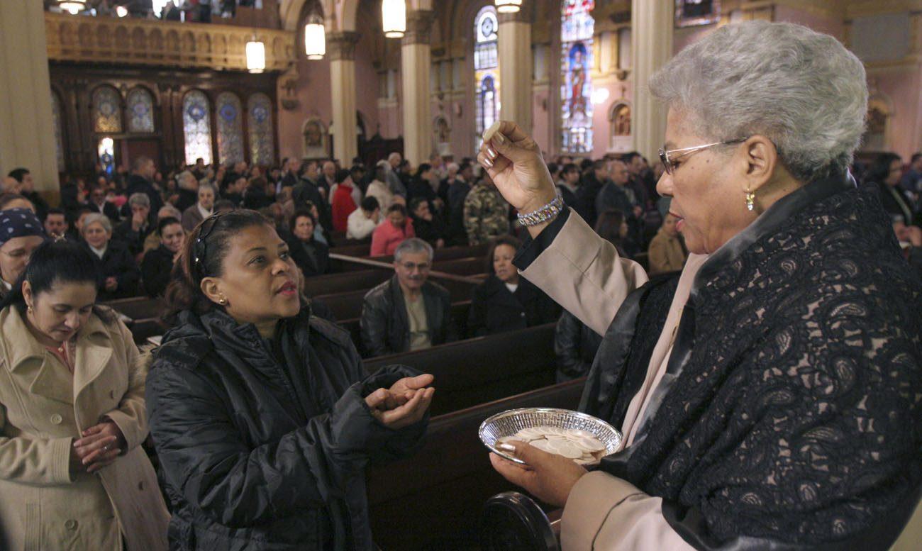 Un ministro eucarístico distribuye la comunión durante la misa de 2008 a Iglesia de la transfiguración en la sección Williamsburg de Brooklyn, Nueva York (SNC foto / Gregory A. Shemitz)