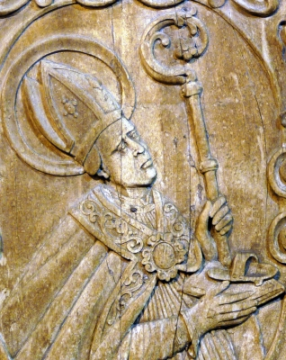 bas-relief carving of Saint Vigilius of Trent on the bottom left panel of the portal of the church of San Pietro, Trent, Italy, date unknown, artist unknown; photographed on 2 March 2010 by Matteo Ianeselli; swiped off Wikipedia
