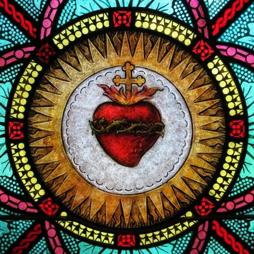 detail of a stained glass window of the Sacred Heart of Jesus, date and artist unknown; All Saints Catholic Church, Saint Peters, Missouri; photographed on 8 July 2014 by Nheyob; swiped from Wikimedia Commons