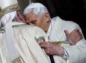 Pope Emeritus Benedict XVI, right, hugs Pope Francis in St. Peter's Basilica during the ceremony marking the start of the Holy Year, at the Vatican, Tuesday, Dec. 8, 2015. Pope Francis pushed open the great bronze doors of St. Peter's Basilica on Tuesday to launch his Holy Year of Mercy, declaring that mercy trumps moralizing in his Catholic Church. (AP Photo/Gregorio Borgia)