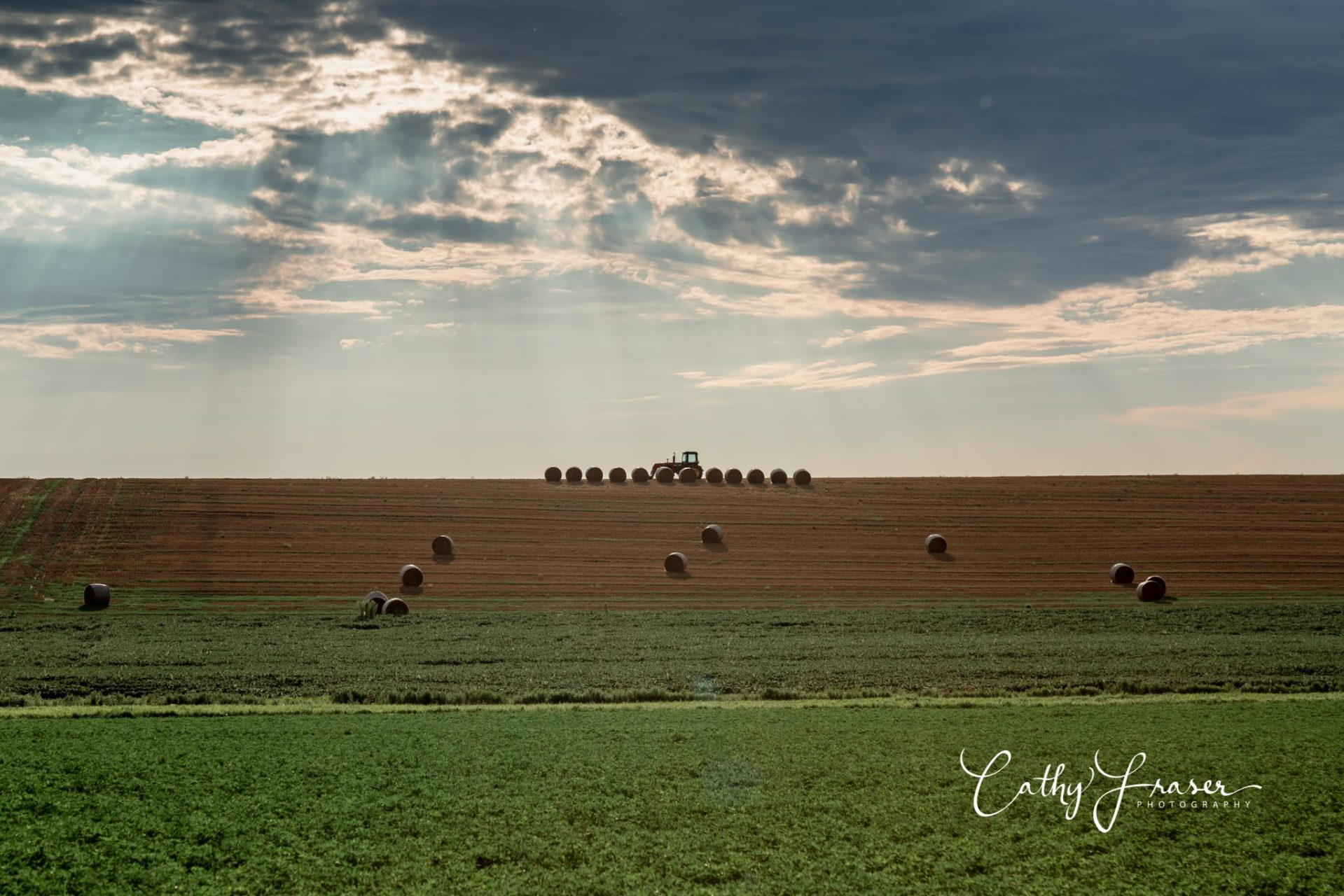 landscape photography of a farm with a tractor and bales of hay in new york